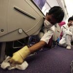 Thai Airways workers clean the cabin of an aircraft of the national carrier at Suvarnabhumi airport in Bangkok April 30, 2009. The World Health Organization warned the world is on the brink of a pandemic, raising its threat level as the swine flu virus spread and killed the first person outside of Mexico, a toddler in Texas. More than 170 people have died since the first cases were reported in Mexico last week.  REUTERS/Chaiwat Subprasom (THAILAND HEALTH TRANSPORT)